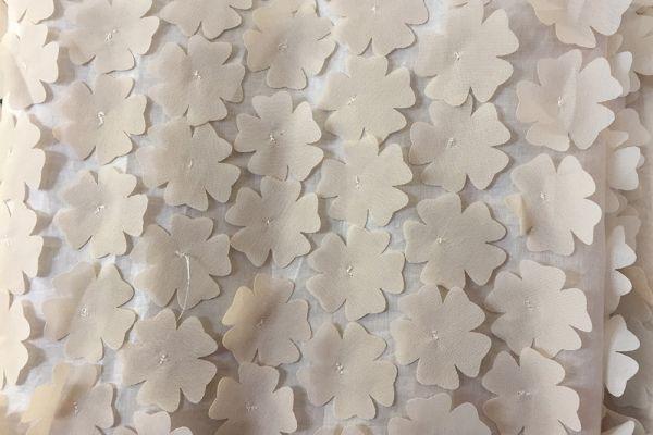 Weiße Blumen auf Vorhang genäht